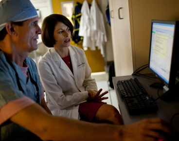 R. David Anderson, M.D., and Julie A. Johnson, Pharm.D., review an alert that appears in a cardiac patient's electronic medical record when genetic results suggest a prescribed drug may not be effective. (Photo by Jesse Jones/University of Florida)